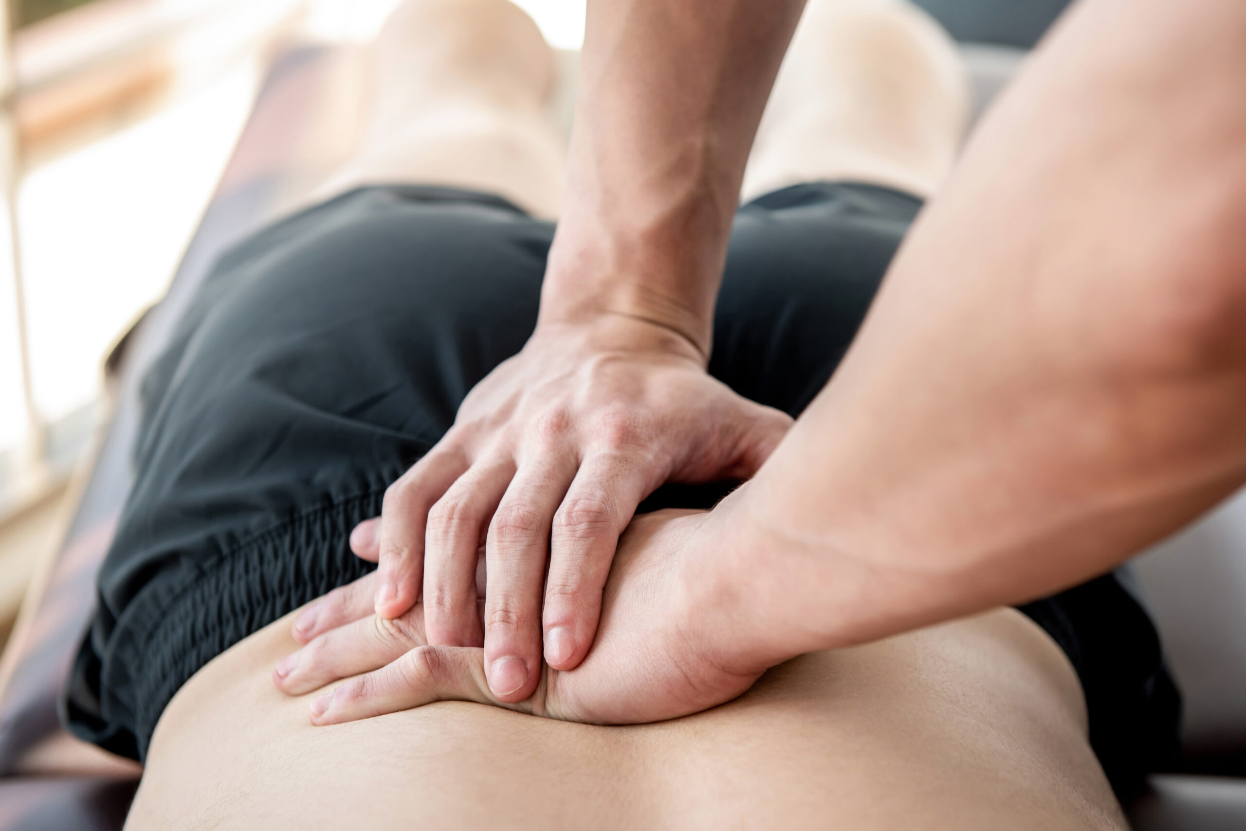 Therapist,Giving,Lower,Back,Sports,Massage,To,Athlete,Male,Patient