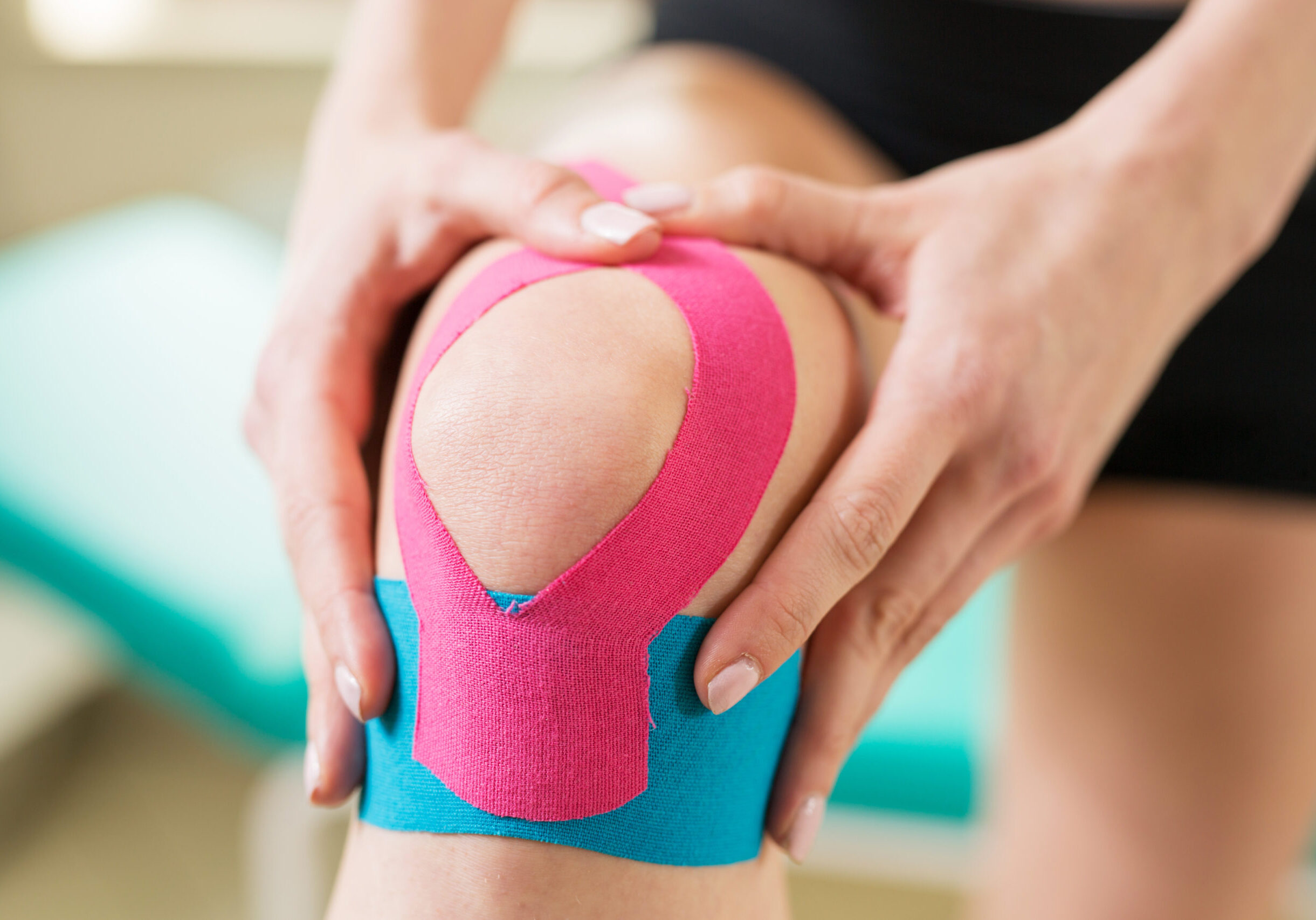 Young,Woman,Massage,Injured,Knee,With,Kinesiotaping
